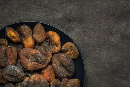sun dried apricots - fruits on a black plate against textured bark paper with a copy spce Stock Photo