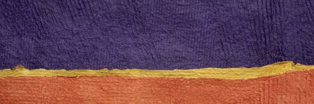 purple and orange - abstract landscape created with colorful sheets of handmade textured paper, panoramic web banner