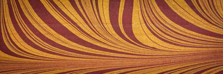 marbled Indian cotton rag paper with red and gold swirls, panoramic web banner Stock Photo