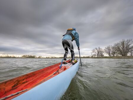 Gone paddling - low angle view from action camera of a male paddler on a long racing stand up paddleboard. Recreation, training and fitness i on a lake on Colorado. Stock Photo
