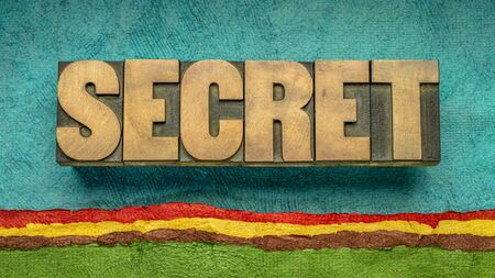 secret word abstract in vintage letterpress wood type against colorful abstract landscape created with textured handmade paper, untold and mystery concept