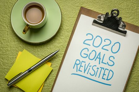 2020 goals revisited  - change of business and personal plans for  coronavirus pandemic and economy recession, handwriting in a clipboard with coffee