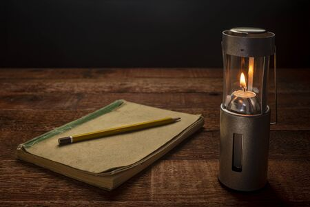 old jornal notebook with acollapsible camping candle lantern burning in darkness on a rustic wooden picnic table