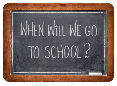 When will we go to school? White chalk hadwriting on a vintage slate blackboard. Schools reopening after coronavirus pandemic concept. Foto de archivo