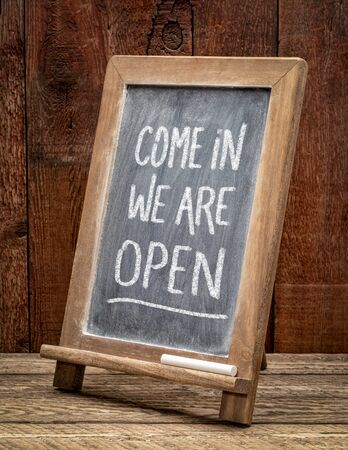 Come in, we are open invitation- white chalk handwriting on a blackboard, business reopening after coronavirus coronavirus pandemic.