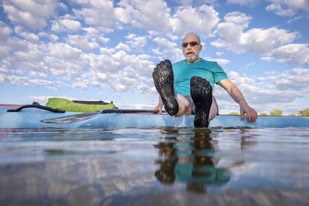 senior male paddler wearing five finger water shoes is sitting on his stand up paddleboard - low angle view from a partially submerged camera Banco de Imagens