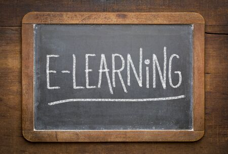 online education concept - e-learning word white chalk writing on a vintage slate blackboard Foto de archivo