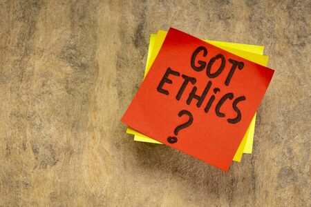 Got ethics? Are you ethical question. Handwriting in a black ink on an sticky reminder note against textured bark paper.