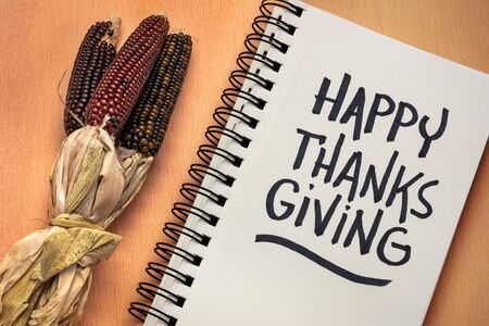 Happy Thanksgiving - handwriting in a notebook with decorative corn, greeting card concept Foto de archivo