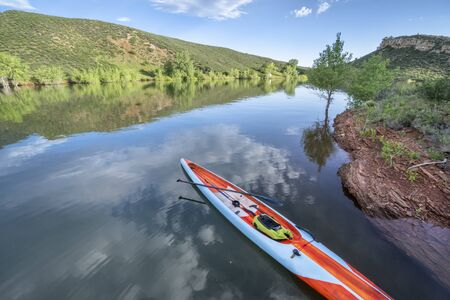 Long and narrow racing stand up paddleboard on a calm mountain lake in early summer - Horsetooth Reservoir in Fort Collins, Colorado, fitness and recreation concept Foto de archivo