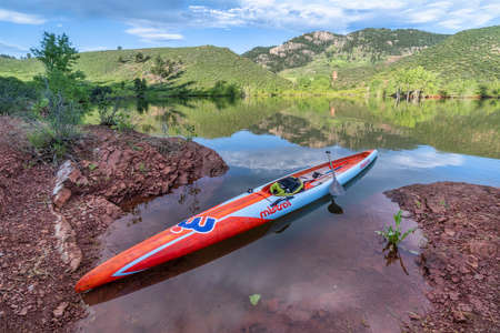 Fort Collins, CO, USA - June 5, 2020: Long and narrow racing stand up paddleboard (Stealth by Mistral SUP) on a calm mountain lake in early summer - Horsetooth Reservoir in Fort Collins, Colorado, fitness and recreaction activity concept.