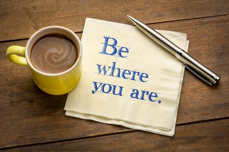 Be where you are  - inspirational handwriting on a napkin with a cup of coffee, be present in the moment reminder