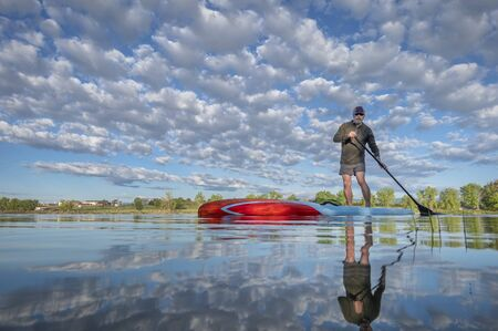 Senior male paddling a stand up paddleboard on a calm lake in Colorado - low angle view from action camera. Recreation, training and fitness concept. Foto de archivo - 149680234