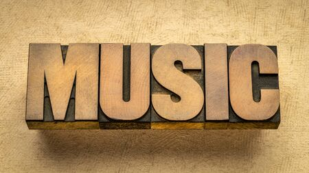 music  - word abstract in vintage wood letterpress printing blocks against textured paper Foto de archivo