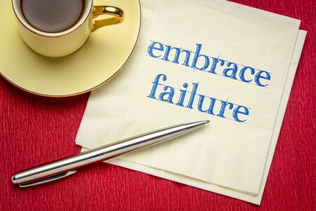 embrace failure inspirational reminder - handwriting on a napkin with a cup of coffee, business or personal development concept Foto de archivo