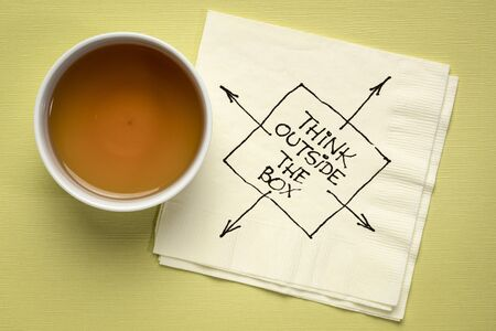 think outside the box inspirational reminder or advice - black pen drawing on a cocktail napkin with a cu of coffee, business, education and personal development concept