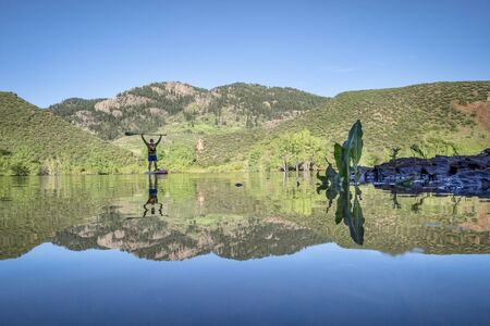 low angle view of male senior paddler on a stand up paddleboard - Horsetooth Reservoir in northern Colorado with Arthurs Rock in background, morning workout and recreation concept