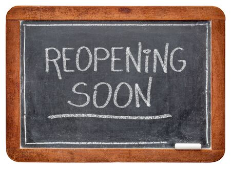 reopening soon - white chalk handwriting on a slate blackboard, business opening after coronavirus covid-19 pandemic and social distancing Foto de archivo - 150339647