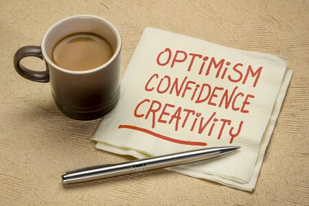 optimism, confidence, creativity inspirational handwriting on a napkin with a cup of coffee, career, lifestyle and personal development concept