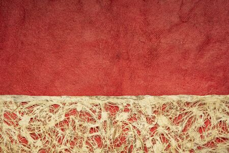 Amate bark paper with lace design against red huun paper.  This ancient paper dates back to pre-Columbian and Meso-American times and is still hand made by the Otomi Indian artisans of Mexico. Foto de archivo - 149956765
