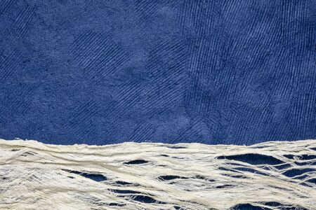 blue sky over snow, sand dunes or whitewater - abstract paper landscape created with a textured Huun paper and a raw mulberry paper Foto de archivo - 150454501