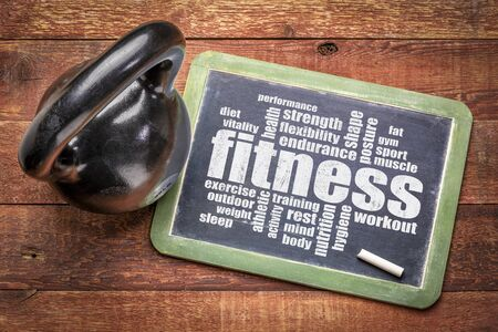 fitness word cloud on a slate blackboard with a kettlebell, workout, training and exercise concept