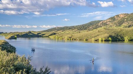 summer morning on  Horsetooth Reservoir at foothills of Rocky Mountains in northern Colorado with a fishing boat and a stand up paddler, popular recreation destination in Fort Collins area Foto de archivo