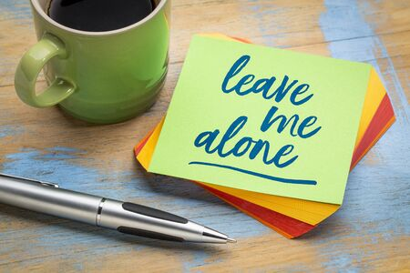 leave me alone  - handwriting on a green sticky note with a pen and a cup of coffee, business and personal issues concept