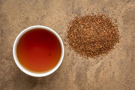 rooibos red tea  -  a white cup of a hot drink and loose leaves, tea made from the South African red bush, naturally caffeine free Foto de archivo - 150520895
