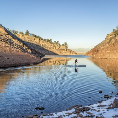Silhouette of a stand up paddler on a mountain lake in winter scenery - Horsetooth Reservoir in northern Colorado, fitness and recreation concept Foto de archivo - 150246780