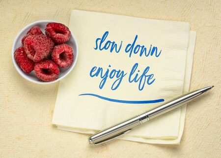 slow down and enjoy life reminder or advice - handwriting on a napkin, lifestyle and reducing stress concept