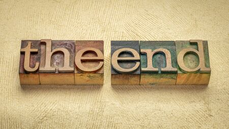 The end concept - words in vintage wooden letterpress printing blocks stained by color inks against handmade textured paper Foto de archivo
