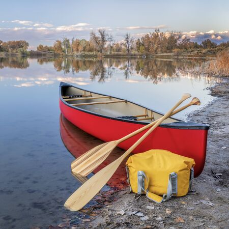 red tandem canoe with a wooden paddles and a dry bag on a lake shore, fall scenery in Colorado