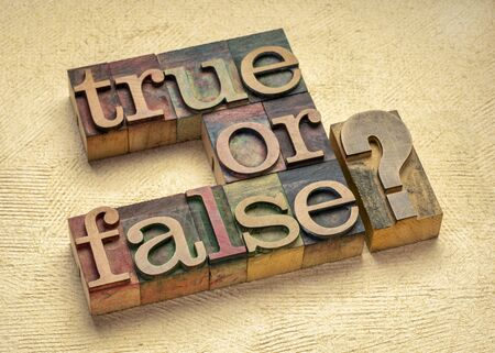 True or false question  in vintage letterpress wood type printing blocks against handmade textured paper, doubt and dilemma concept