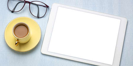 digital tablet with white blank screen, cup of coffee, reading glasses - flat lay concept