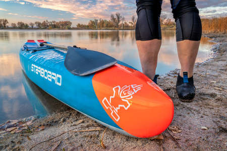 Fort Collins, CO, USA - October 17, 2018:  Male paddler with a racing stand up paddleboard on calm lake in fall scenery in northern Colorado - 2016 All Star race design by Starboard