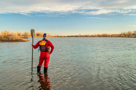 male stand up paddler dressed in a drysuit and life jacket for cold season paddling is contemplating lake view in Colorado, sport and recreation concept Foto de archivo
