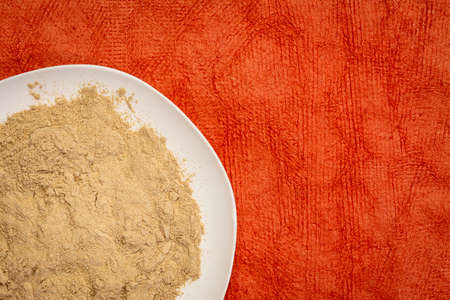 maca root powder on white ceramic plate against red textured paper, superfood concept