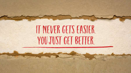 It never gets easier, you just get better - inspirational handwriting on handmade paper, business, education and personal development concept, web banner Foto de archivo