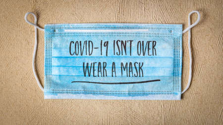 covid-19 is not over, wear a face mask - text on a disposable mask against textured paper, business sign during the coronavirus covid-19 pandemic and social distancing Standard-Bild
