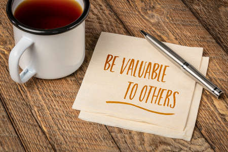 Be valuable to others - inspirational advice, handwriting on a napkin with a cup of tea, business, relationships and personal development concept