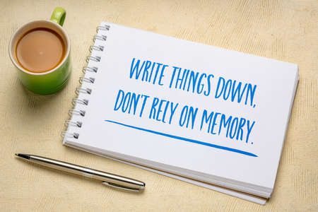 write things down, do not rely on memory - productivity advice, handwriting in a sketchbook with a cup of coffee, business, education and personal development concept 版權商用圖片