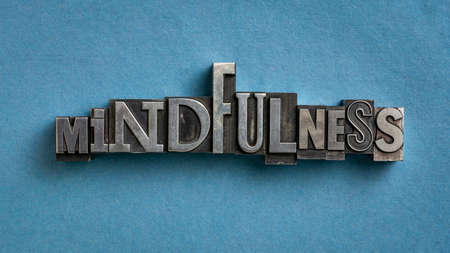 mindfulness word abstract or banner - awareness concept - text in vintage letterpress metal type against blue textured paper