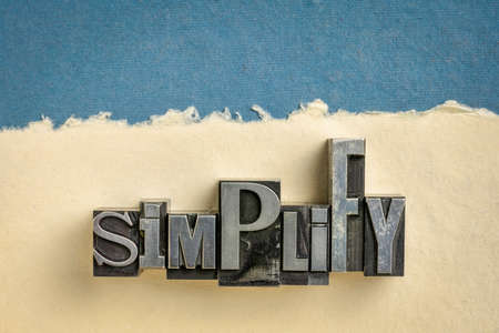 simplify - word abstract in vintage letterpress metal type printing blocks against handmade paper, organize and declutter concept Banco de Imagens