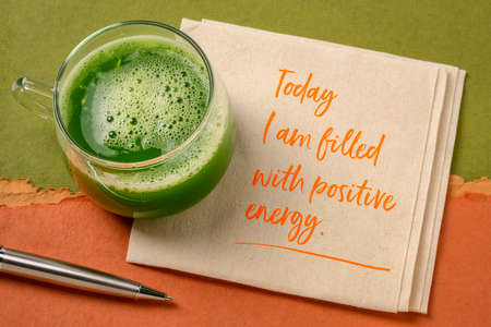 today I am filled with a positive energy - inspirational note on a napkin with a glass of fresh green cucumber juice, lifestyle and positivity concept Banco de Imagens