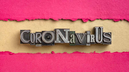 coronavirus word abstract in vintage letterpress metal type against handmade paper, covid-19 virus outbreak and pandemic concept