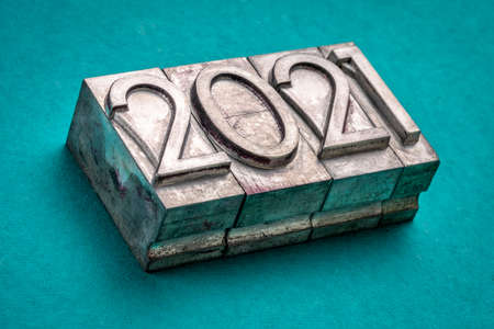 2021 year in vintage, gritty letterpress metal type against turquoise handmade paper, New Year concept