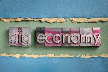 gig economy word abstract in gritty letterpress metal type against handmade paper, business and finance concept