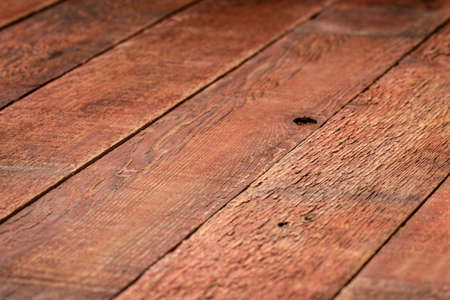 rustic wooden background with a selective focus - diagonal planks of weathered pine red painted wood with strong grain, sawing pattern and knots