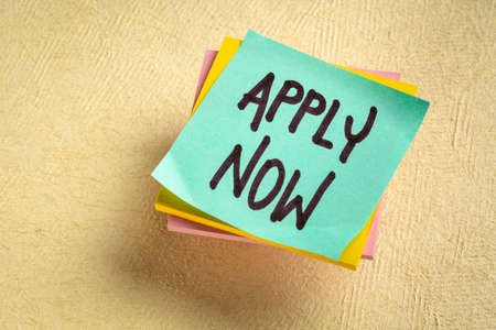 Apply now - handwriting on a reminder note, business marketing concept